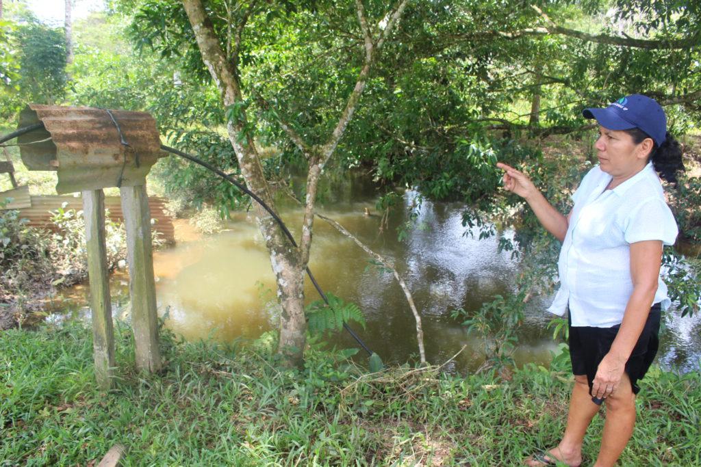 Gladys Hurtado, de la comunidad San Juan del Pozo, señala el arroyo ubicado en la parte posterior de su vivienda, del que se abastece de agua y llega contaminado con hidrocarburos. Foto: Daniela Aguilar