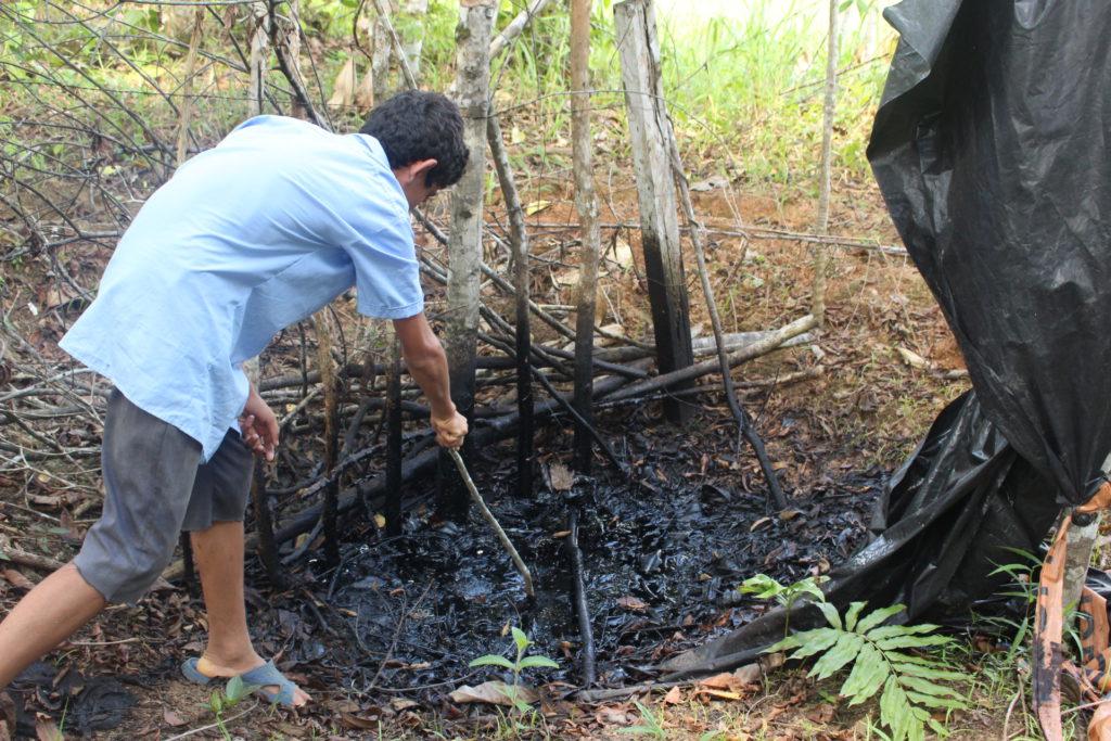 Anderson Calero remueve desechos petroleros ubicados dentro de la propiedad de su familia. Dice que toda el área está comprometida.